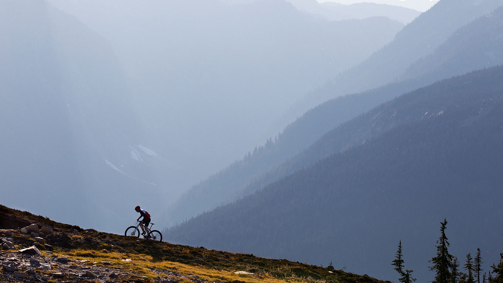 Cyclist heading up a hill in a mountain range