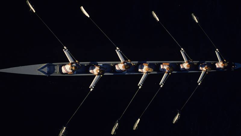 Team of 8 rowing at night